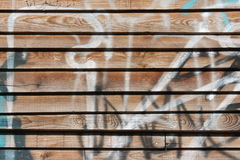 Graffiti on wooden wall. Close-up view of an old wooden wall with paint and graffiti royalty free stock photos
