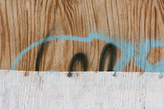Graffiti on wooden wall. Close-up view of a wooden surface with paint and graffiti stock photography