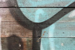 Graffiti on a wooden wall. Close-up view of a weathered wooden wall with paint and graffiti fragments royalty free stock images