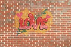 A graffiti of the word love on a background of a wall with bricks. With hearts and leaves and berries. In the colors red pink yellow green white and brown. n royalty free stock photo