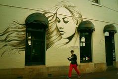 A graffitied het huis-portret van een mooie vrouw op de muur stock foto's