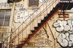 Graffitied trappuppgång i gatagränd Arkivbild