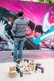 Graffitikunstenaar die de muur bespuiten Stock Foto