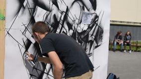 Graffitikunstenaar die in de straat werken stock footage