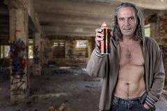 Graffitikunstenaar in een geruïneerd gebouw illegaal wordt verlaten dat Beauti stock foto
