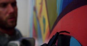 Graffitikunstenaar het schilderen met teller op de muur 4k stock videobeelden