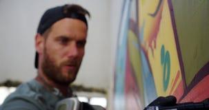 Graffitikunstenaar het schilderen met teller op de muur 4k stock video