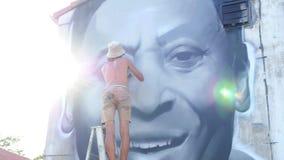 Graffitikunstenaar Painting Graffiti op de Muur binnen stock footage