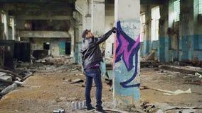 Graffitimaler in der Freizeitbekleidung zeichnet mit Sprühfarbe auf Spalte im geräumigen verlassenen Gebäude Auszug stock video footage