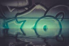 Graffitireflexion im Wasser, künstlerische Chrombuchstaben Lizenzfreie Stockfotos
