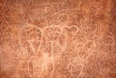 Graffitis och skrapor på den breda rostiga väggen Arkivbilder
