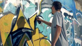 A graffitist freshens up the picture. A graffitist comes closer to a graffiti wall to renew the picture stock video footage