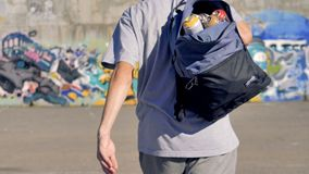 A graffitist puts on an open backpack full of paint cans. stock footage