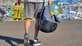 A graffitist takes a backpack with paints in one hand. A low view on a man carrying an open backpack with spray paints stock footage
