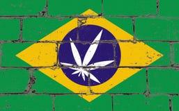 Graffitistraßenkunst-Sprayzeichnung auf Schablone Hanfblatt auf Backsteinmauer mit Flagge Brasilien stockfotos