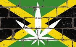 Graffitistraßenkunst-Sprayzeichnung auf Schablone Hanfblatt auf Backsteinmauer mit Flagge Jamaika stockbilder