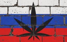 Graffitistraßenkunst-Sprayzeichnung auf Schablone Hanfblatt auf Backsteinmauer mit Flagge Russland stockbild