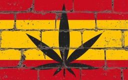 Graffitistraßenkunst-Sprayzeichnung auf Schablone Hanfblatt auf Backsteinmauer mit Flagge Spanien stockfotografie