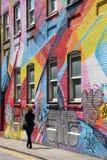 Graffitistraat met vrouw het lopen Stock Foto