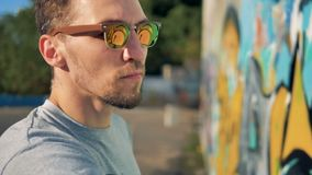 A graffitists face in reflective glasses at work. A close-up on graffitists face as he works on a wall during daytime stock footage