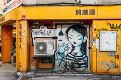 Graffitti sur le mur du bâtiment jaune avec la traction au-dessus de la bicyclette à Sapporo au Hokkaido, Japon Images libres de droits