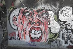 Graffiti depicting a distorted human face. Graffti on a wall depicting a distorted human face with open mouth Royalty Free Stock Images