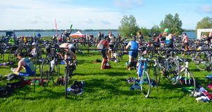 Triathletes at end of swimming stage in change over area with bicycles. stock photos