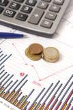 Grafici con la penna e calcolatore e monete Immagini Stock Libere da Diritti