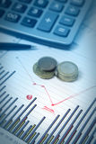 Grafici con la penna e calcolatore e monete Fotografia Stock Libera da Diritti