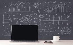 Grafici di affari e computer portatile finanziari dell'ufficio Fotografie Stock Libere da Diritti