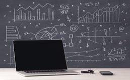 Grafici di affari e computer portatile finanziari dell'ufficio Fotografia Stock