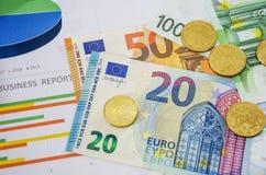 Grafici di affari, euro e monete, primo piano Vista da sopra fotografie stock libere da diritti