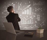 Grafici di vendite del disegno dell'uomo d'affari sulla parete Immagine Stock