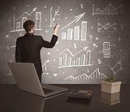 Grafici di vendite del disegno dell'uomo d'affari sulla parete Fotografie Stock