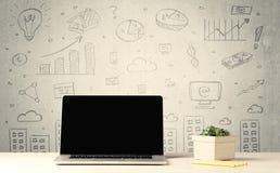 Grafici e computer portatile urbani di vendite sullo scrittorio Fotografia Stock