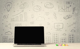 Grafici e computer portatile urbani di vendite sullo scrittorio Fotografie Stock