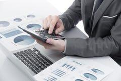Grafici e grafici analizzati dall'uomo d'affari Immagini Stock