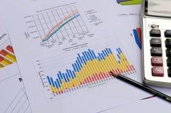 Grafici e grafici di affari con la penna ed il calcolatore Fotografie Stock Libere da Diritti