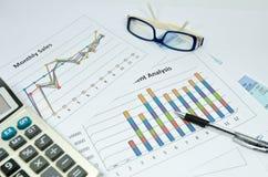 Grafici e grafico di affari con l'occhio e la penna di vetro Fotografie Stock
