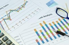 Grafici e grafico di affari con l'occhio e la penna di vetro Fotografia Stock Libera da Diritti