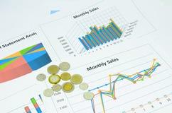 Grafici e grafico di affari con le monete Immagine Stock
