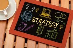 Grafici ed icone di strategia aziendale sulla lavagna Immagini Stock