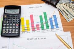 Grafici, grafici, tavola di affari con soldi, calcolatore e penna Immagini Stock Libere da Diritti