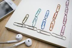 Grafici, telefono e cuffia delle graffette su un taccuino e sulle sedere di legno fotografia stock