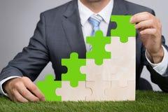Grafico del puzzle della tenuta dell'uomo d'affari su erba Fotografia Stock