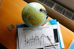 Grafico delle figure di dati accanto al globo Immagine Stock