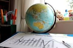 Grafico delle figure di dati accanto al globo Fotografia Stock