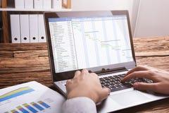 Grafico di Working With Gantt della persona di affari sul computer portatile fotografia stock libera da diritti