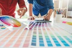 Grafico due che attinge la guida della tavola dei grafici e della tavolozza di colore nel luogo di lavoro immagini stock libere da diritti