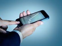 Grafico e statistiche del telefono cellulare di tocco dell'uomo d'affari che aumentano sullo Sc Fotografie Stock Libere da Diritti